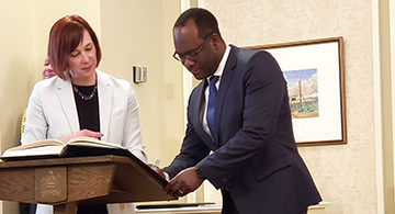 Kaliche Madu signs his appointment paper during the swearing in of the new Alberta Cabinet Ministers